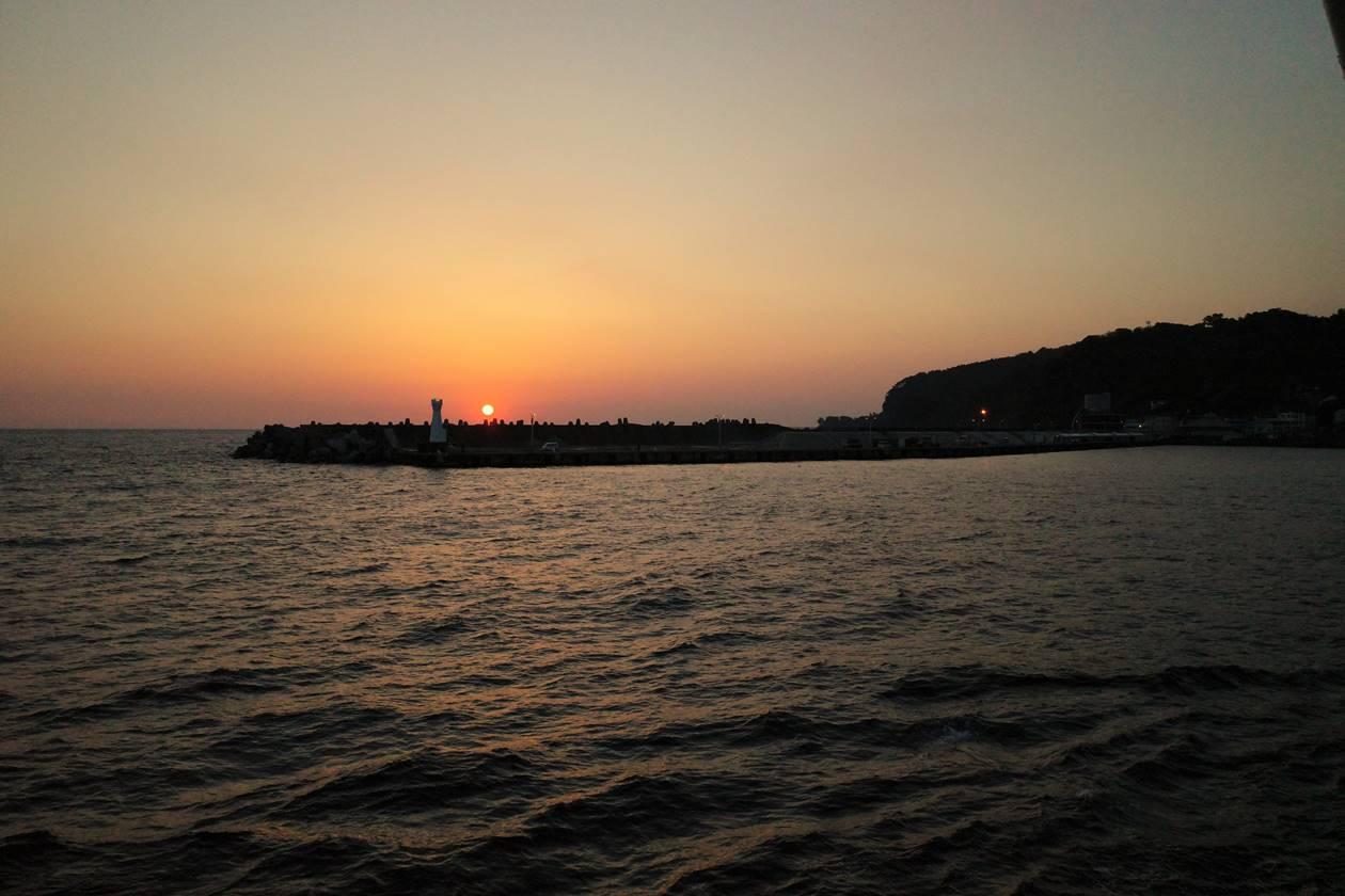 海から眺める伊豆大島と日の出