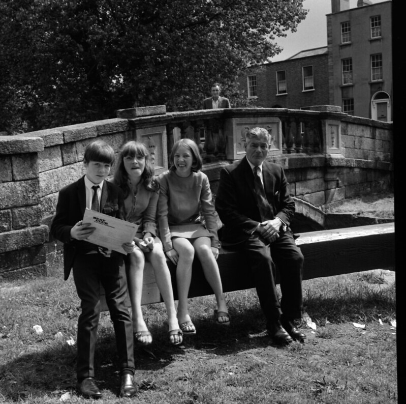 Young people and man sitting on lock gate at Huband Bridge, Grand Canal, Dublin