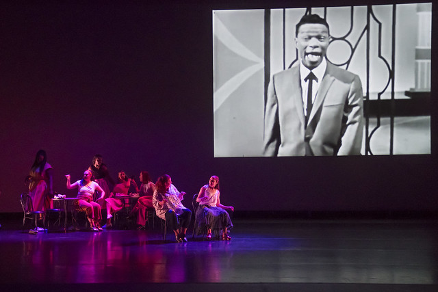 A group of dancers sits in chairs around a table while a video of Nat King Cole plays on stage during a production of Dancing Community.