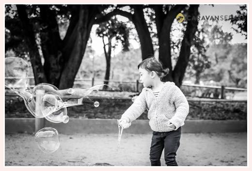 公園でシャボン玉をする女の子 モノクロ写真
