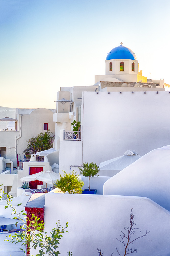 People Travelling. European Destinations. Ancient Famous Blue Dome of Oia Village Church on Santorini Island in Greece.