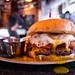 Burger w/ cheddar, Canadian bacon, garlic aioli, hash brown, pickled onion, and egg - Table 9