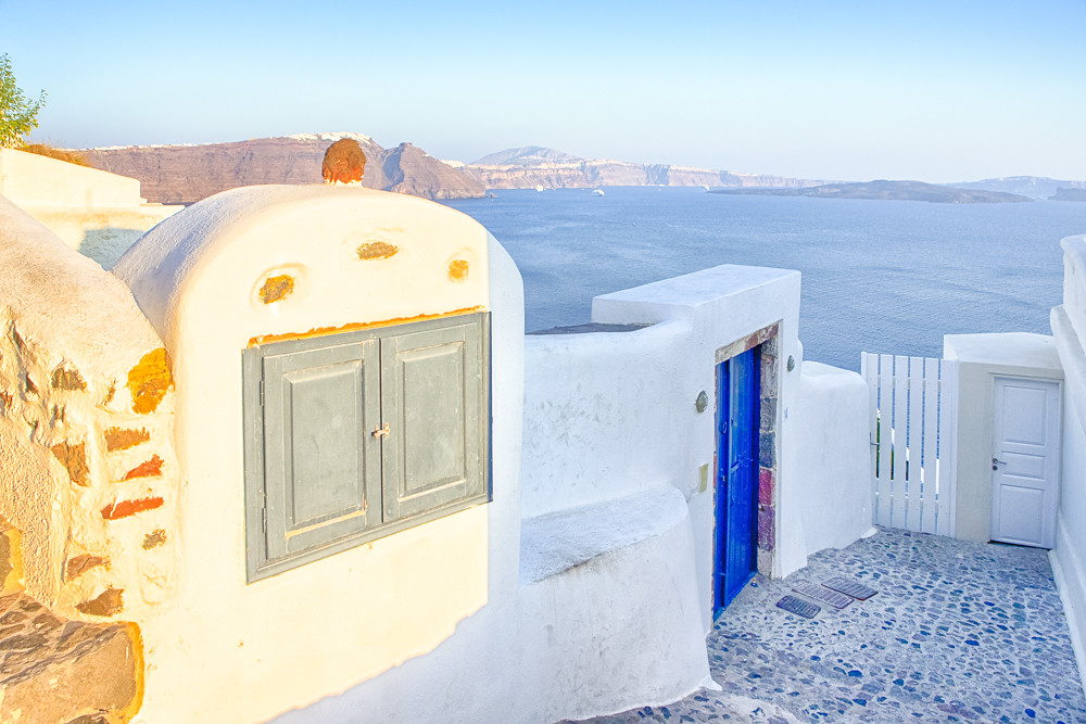 European Travel Destinations.Picturesque Houses and  Paved Stairs of Oia Village in Santorini with Volcanic Caldera and Sailing Boats on Background.