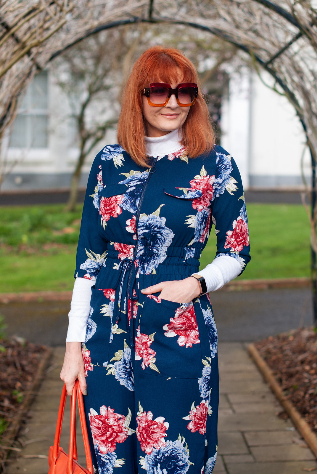 Fashion Over 40: How to Layer a Jumpsuit in Spring (and a Touch of the Elton John) \ navy and red floral jumpsuit \ white roll neck sweater \ burgundy slouch boots \ navy pinstripe coat \ Elton John-style sunglasses | Not Dressed As Lamb style blog