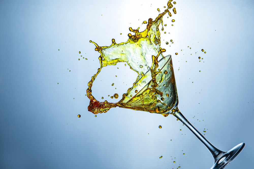 Fast Action Photography. Alcohol Drink Colorful Droplets Falling Out of Clear Wine Glass.