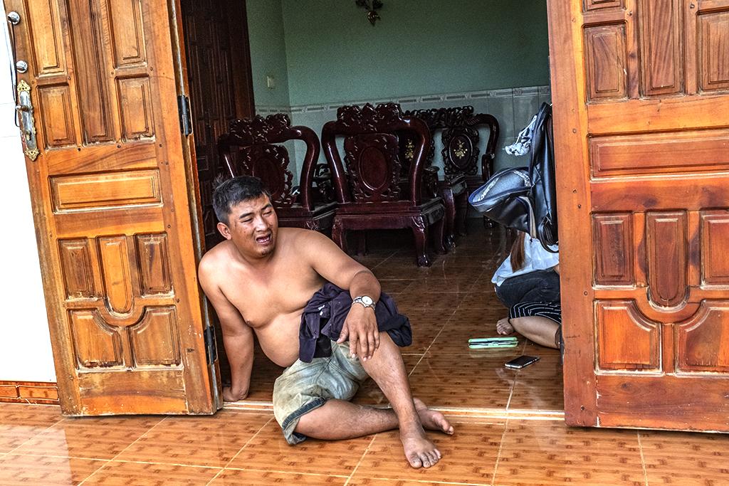 Fat man sitting in doorway--Krong Buk