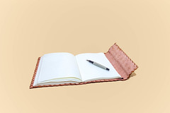 Leather notepad with blank pages and pen on cream background