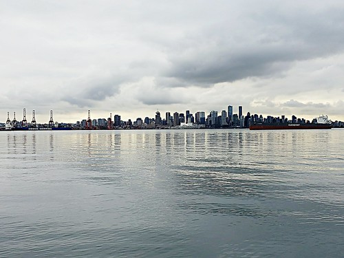vancouver britishcolumbia canada downtown cbd skyline cityscape portofvancouver port inlet water pacificocean burrardinlet sea ocean waves clouds grey christmasday december25 2018 winter december sky buildings view scenery cranes ships boats canadaplace reflections light dark gloomy threateningsky