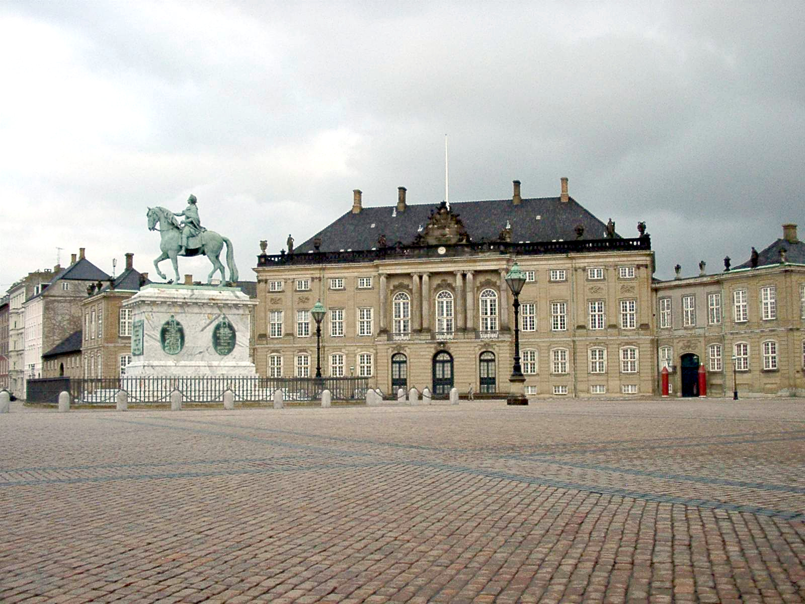 Princess Margrethe's birthplace: Frederik VIII's Palace at Amalienborg in Copenhagen, Denmark. It consists of four identical classical palace façades with rococo interiors around an octagonal courtyard (Amalienborg Slotsplads); in the center of the square is a monumental equestrian statue of Amalienborg's founder, King Frederick V. Photo taken by Wolfgang Hägele on November 25, 2003.