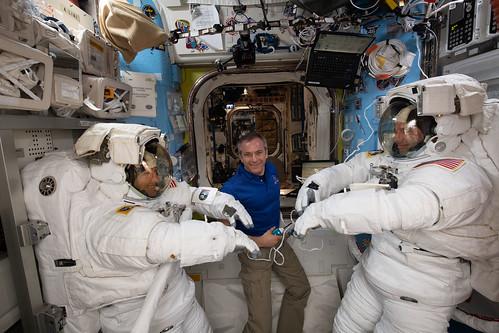 Astronaut David Saint-Jacques assists fellow astronauts Christina Koch (left) and Nick Hague