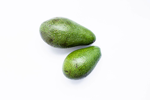 Top view of two whole ripe avocados on white background