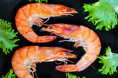 Three large prawns with lettuce leaves