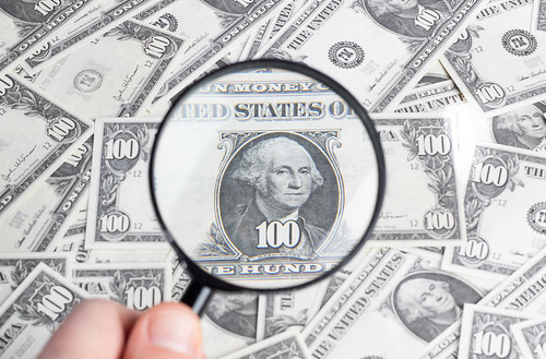 Magnifying glass on dollar banknotes