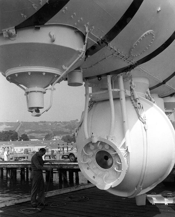 Close up view of the front of Trieste's pressure sphere, showing plexiglass window and instrument leads. The forward ballast silo, with metering valve on its bottom, is in the upper left. Photo was taken circa 1958-59, shortly after Trieste was obtained by the Navy. It was released by the U.S. Navy Electronics Laboratory, San Diego, California. U.S. Naval Historical Center Photograph #NH 96805