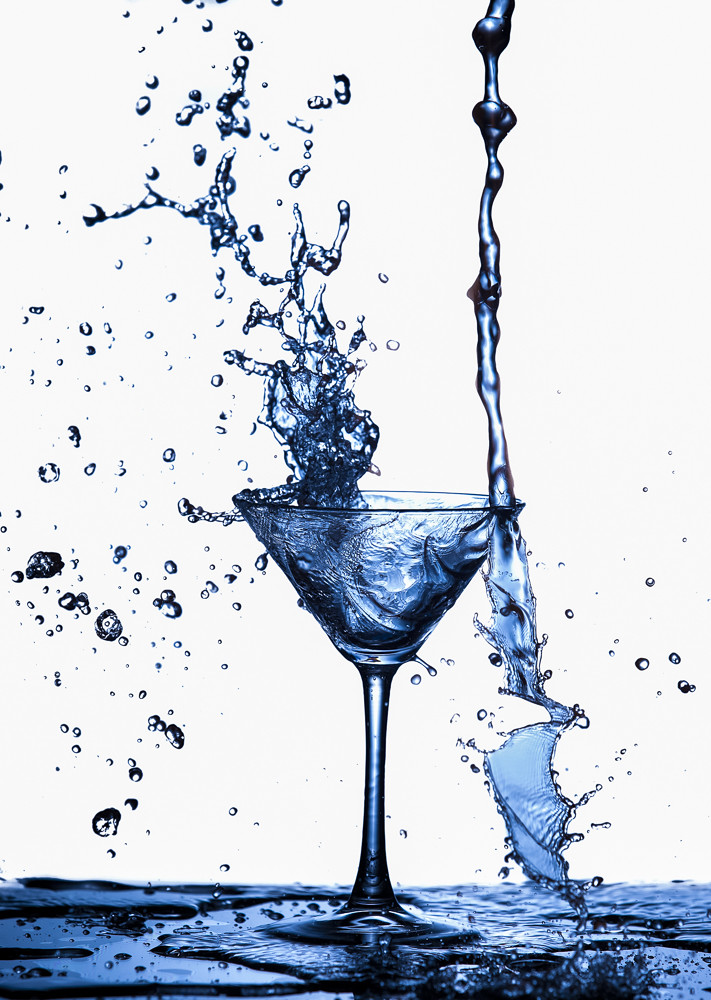 Clear Wineglass With Burst of Water Splashes In Motion Against Pure White Background.