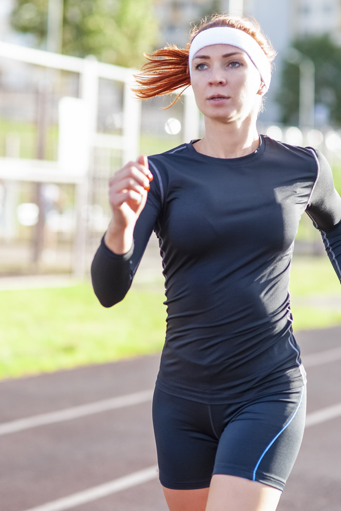 Fitness and Healthy Lifestyle Concepts. Female Athlete Having Running Exercise Outdoors.