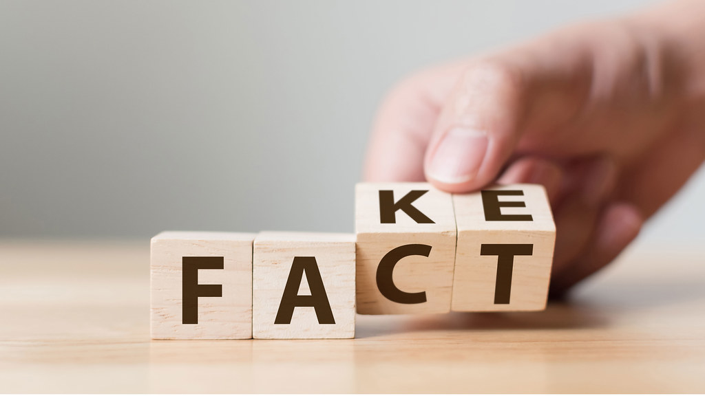A hand moving some blocks displaying the text 'fact' and 'fake'.