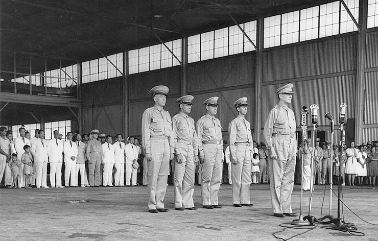 Ceremony at Camp Murphy, 15 August 1941, marking the induction of the Philippine Army Air Corps. Behind MacArthur, from left to right, are Lieutenant Colonel Richard K. Sutherland, Colonel Harold H. George, Lieutenant Colonel William F. Marquat and Major LeGrande A. Diller.