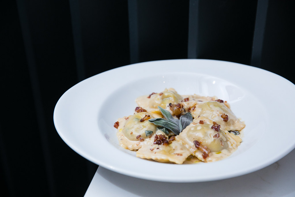 Porchetta Ravioli is doused with a creamy parmesan sauce and contrasted with sweet maple pancetta