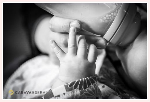 赤ちゃん 哺乳瓶を持つ小さな手 モノクロ写真