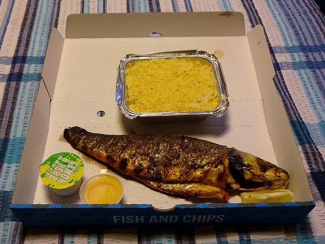 An opened-out shallow cardboard box with a nicely-grilled whole fish laid out across it.  A couple of small plastic sauce pots are in one corner, and a foil container of yellow rice is placed next to the fish.