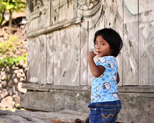 Niño paseando junto a una casita de madera en la aldea de Batad