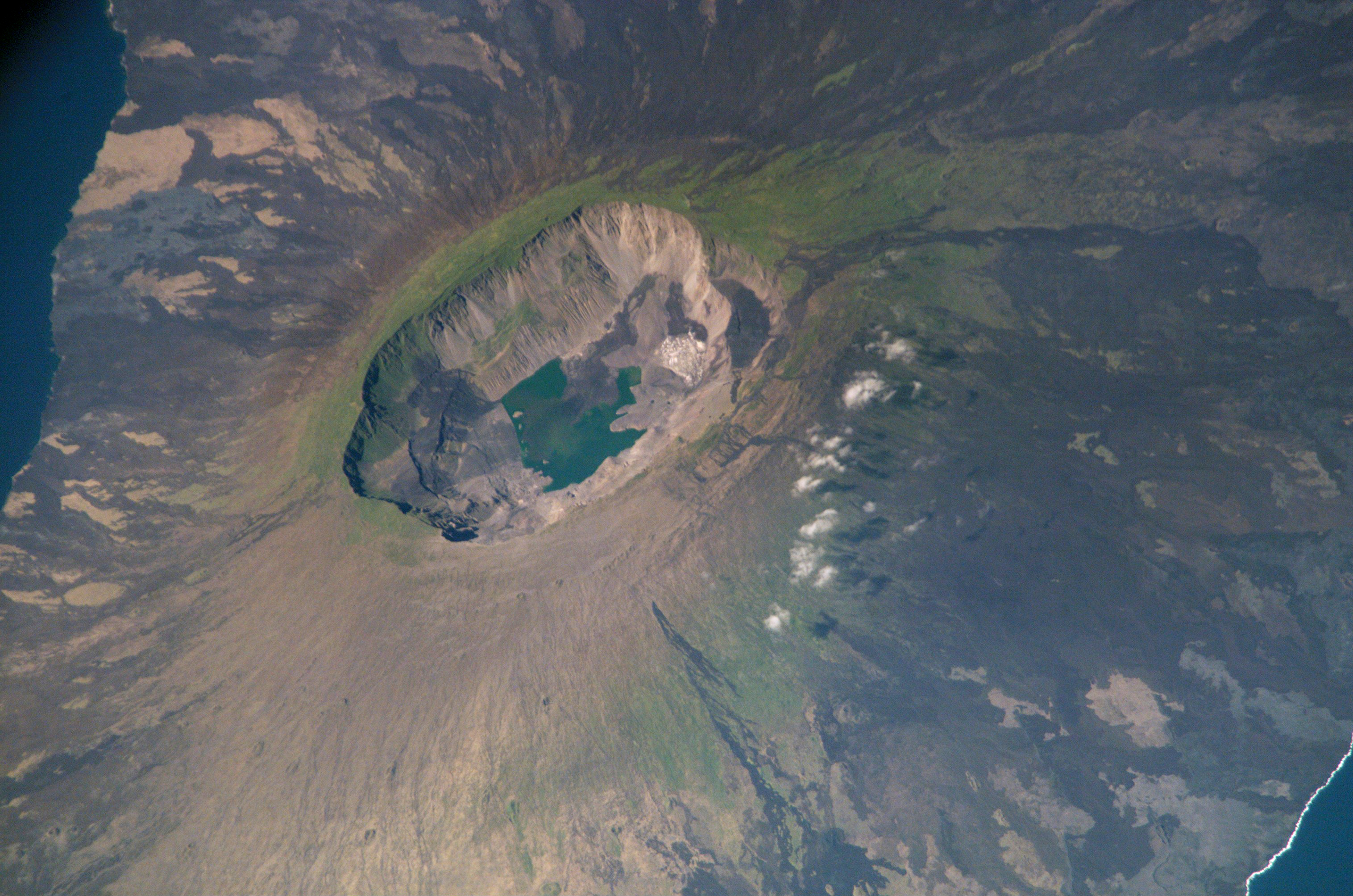 La Cumbre volcano on Fernandina Island is the most active volcano on the Galapagos, erupting most recently on June 16, 2018. The volcano rises 4,842 feet (1,476 m) above sea level. This photo was taken by the Expedition 5 crew aboard the International Space Station on July 6, 2002. The scene provides a detailed view of the 850-m-deep summit caldera. The dark flows in the middle of the caldera floor were erupted in 1991. Today, these flows are partly covered by dark green vegetation.