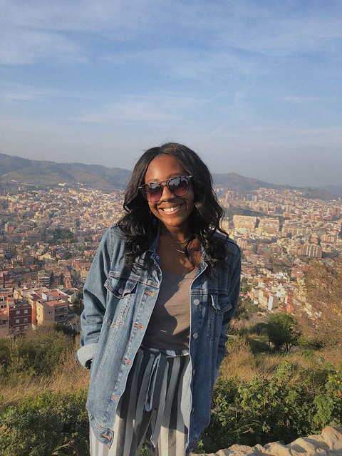 Student in standing on an overlook of Barcelona and the mountains behind the city.