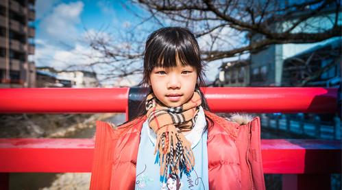 Girl crossing red bridge towards the old town in Takayama