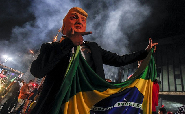 "A Trump doll holds the Brazilian flag and does Jair Bolsonaro's signature ""guns up"" hand gesture - Créditos: Miguel Schincariol/AFP"
