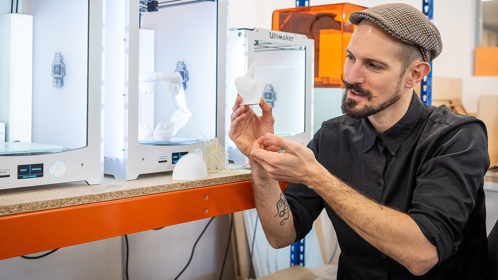A student sits in front of 3D printers holding a 3D printed phytoplankton