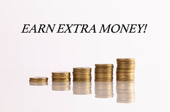 Stacks of coins with Earn extra money text