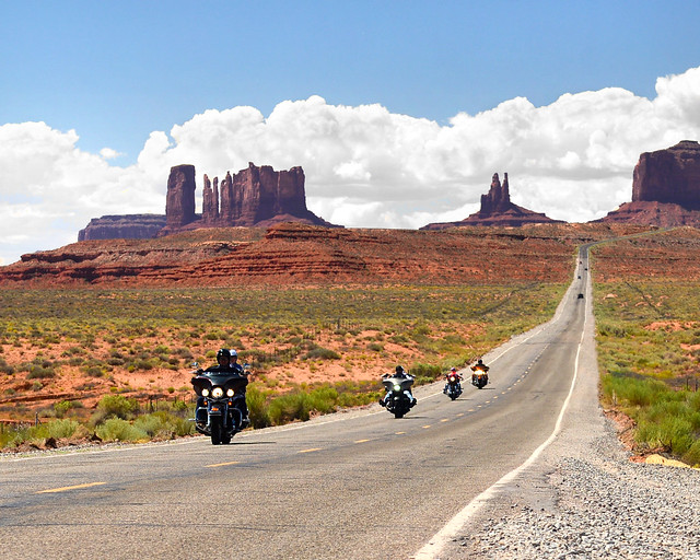 Moteros conduciendo por la carretera de Forrest Gump en Monument Valley