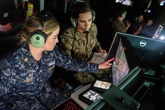 Chief Operations Specialist Anna Penrod, left, assigned to USS Rafael Peralta (DDG 115), and Lt. Aaron Van Driessche participate in an air defense scenario, Jan. 10. (U.S. Navy/MC2 Nicholas Burgains)