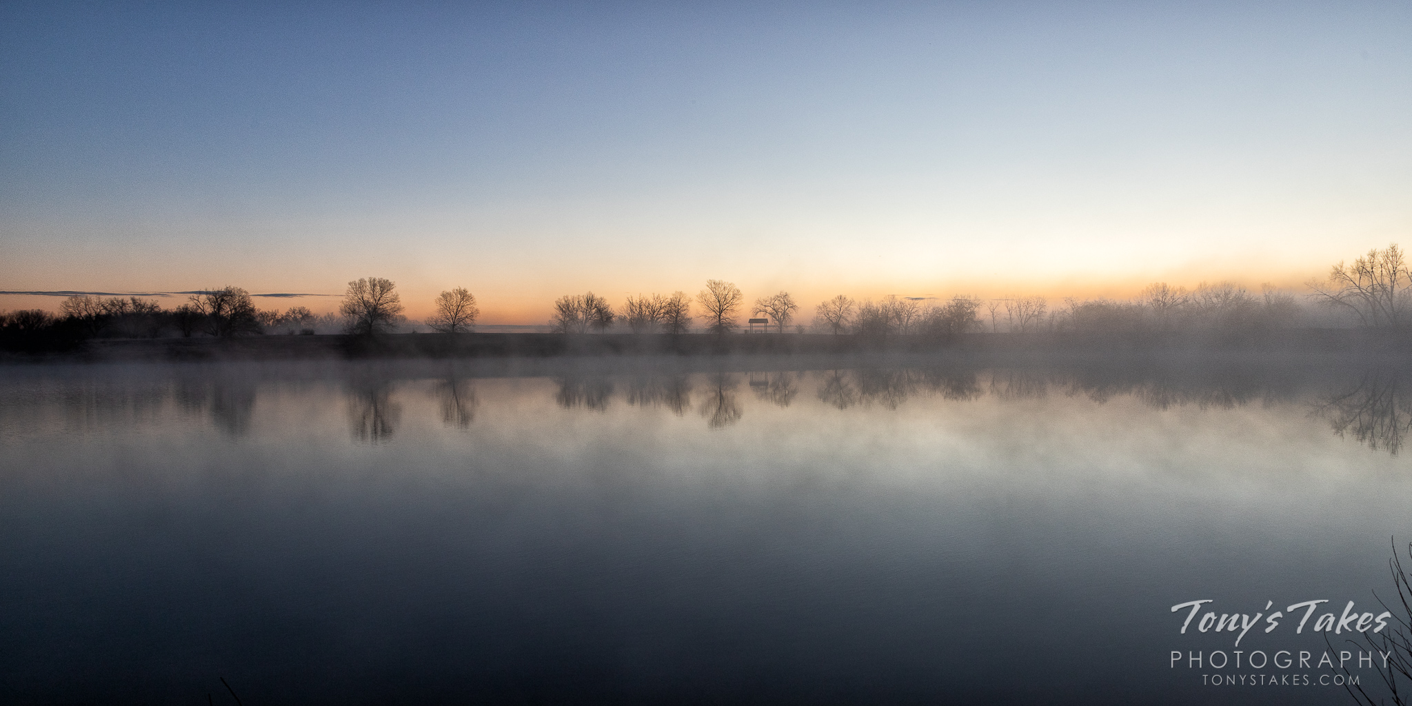 The sun begins to color the horizon as fog gathers on a pond in Adams County, Colorado. (© Tony's Takes)