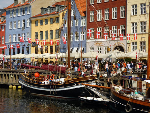 Bright houses and busy pedestrian streets in the district of Nyhavn in Copenhagen, Denmark