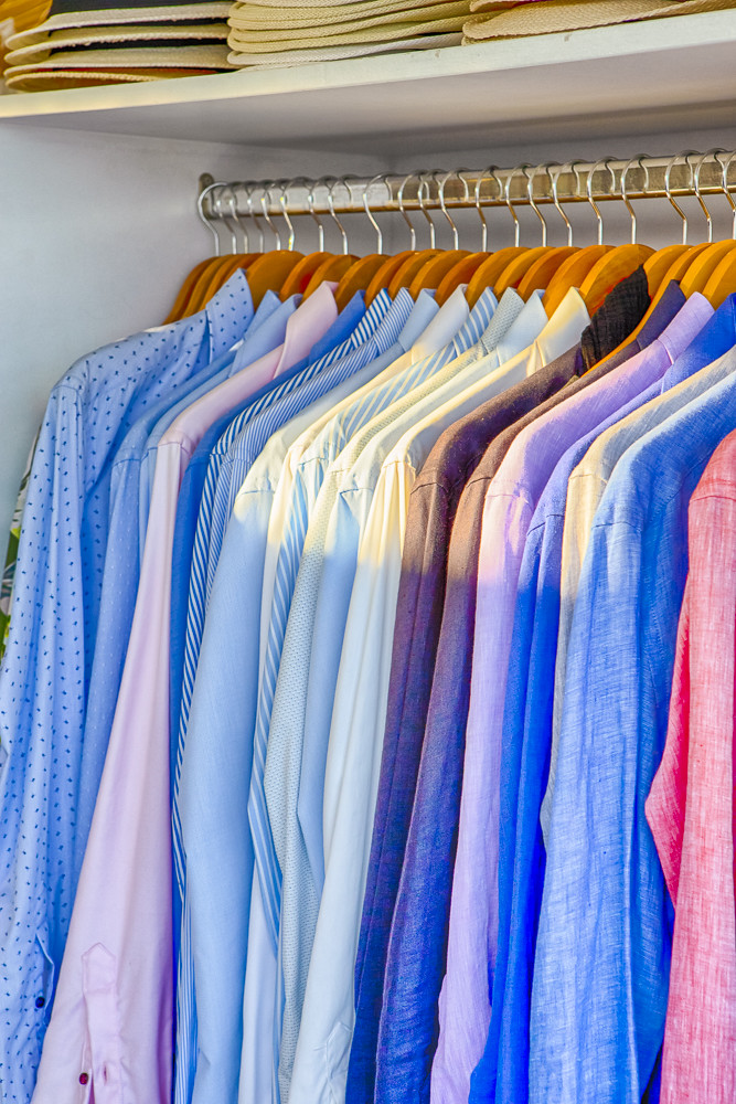 Line of Colorful Linen Summer long Sleeve Shirts Placed on Hangers in Store of Oia Village in Santorini Island in Greece.
