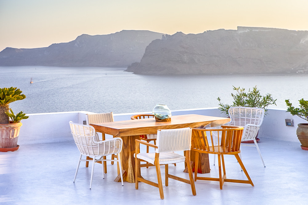 Tranquil and Romantic Atmosphere at Open Air Terrace Restaurant in Beautiful Oia Village on Santorini Island in Greece in Front of Volcanic Caldera Mountain.