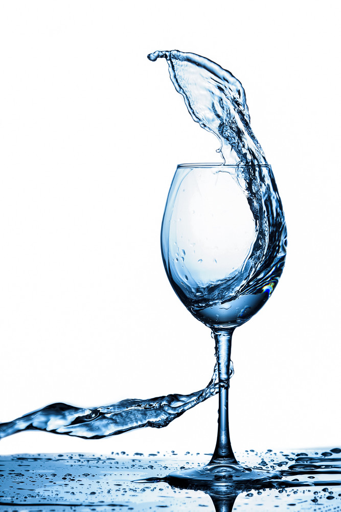 Clear Wineglass With Bluish Water Splash In Motion Against Pure White Background.