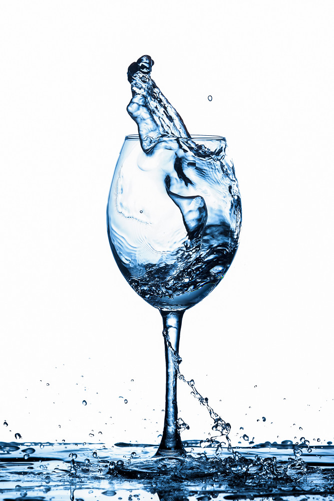 Clear Wineglass With Bluish Water Splash and Drops In Motion Against Pure White Background.