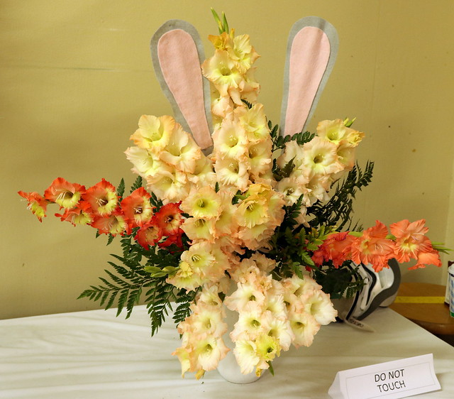 An arrangement of peachy-cream flower stems, with 2 orange stems at the 3 and 9 o'clock positions, and long rabbit ears at the top.