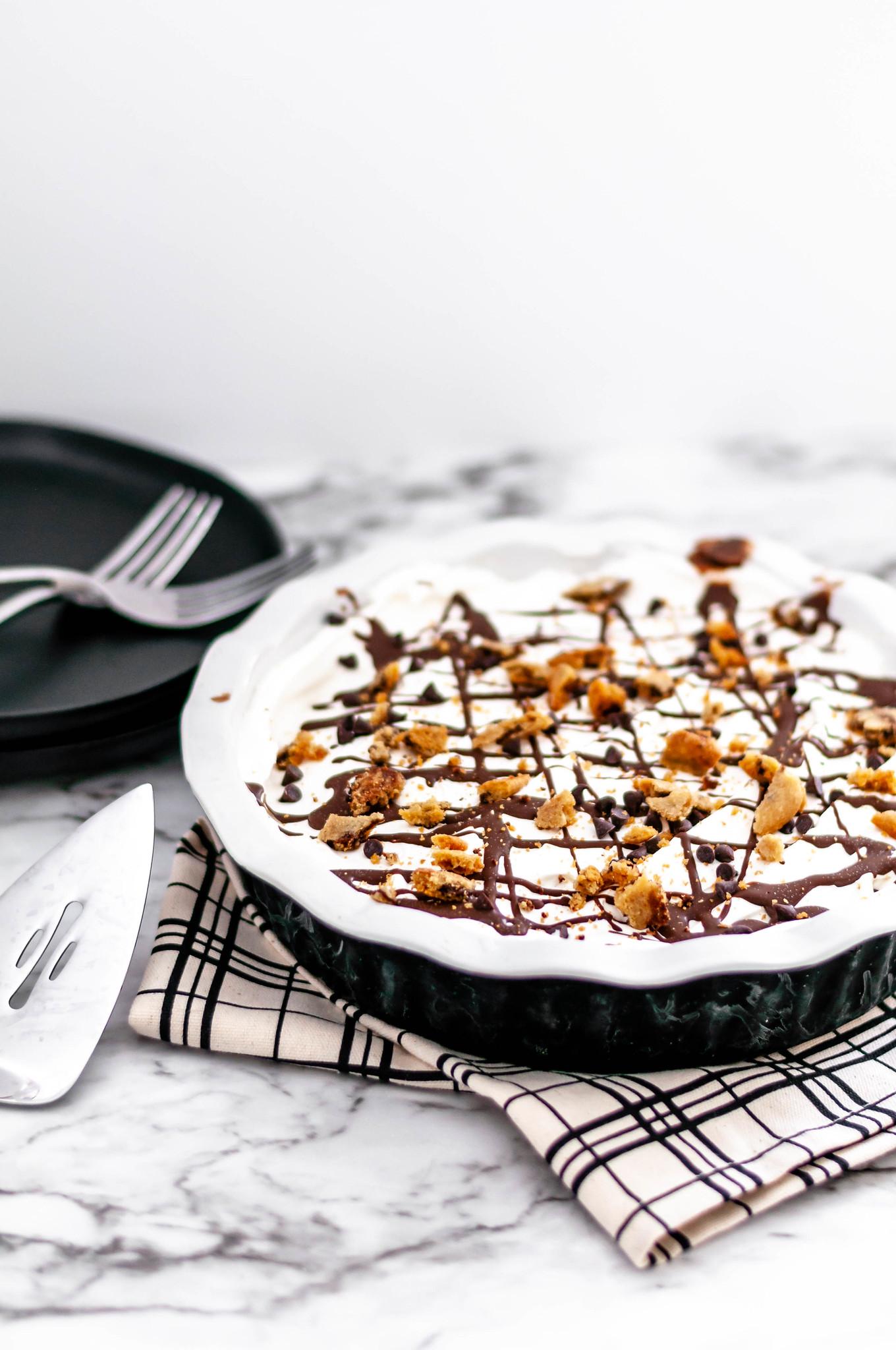 Chocolate Chip Cookie Dough Ice Cream Pie is the ultimate dessert. Cookie dough crust, cookie dough ice cream, whipped cream and chocolate syrup.