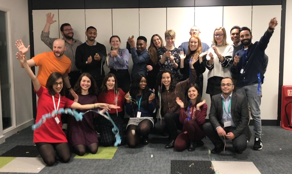 UK National Agency staff celebrating International Women's Day by pulling party poppers and striking the #BalanceForBetter post