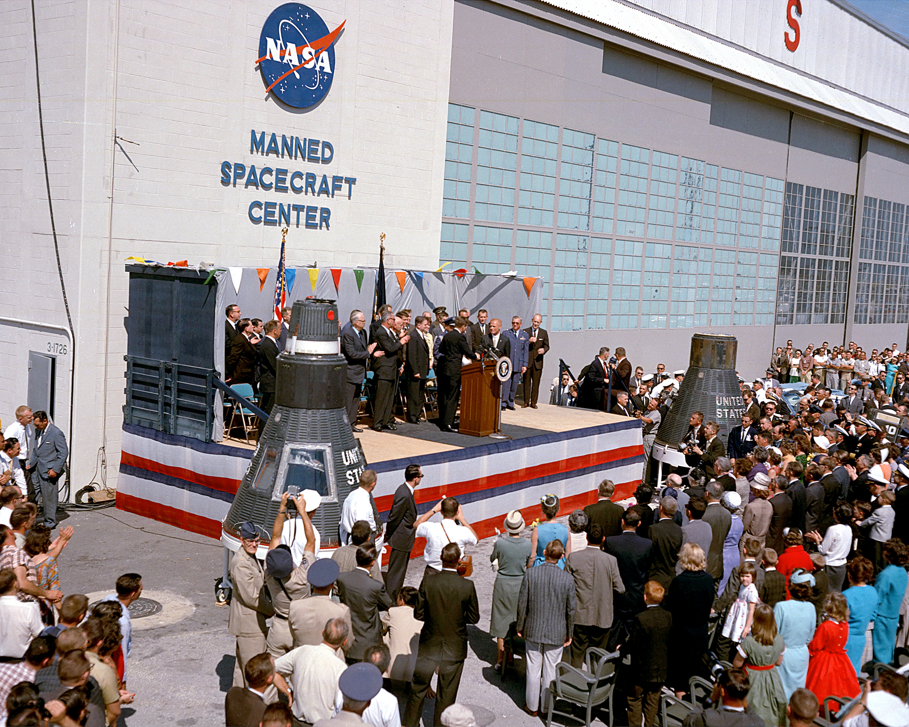 Astronaut John Glenn, Jr. is honored by President John F. Kennedy after his historical first manned orbital flight. The ceremony is being held at Hanger S at Cape Canaveral, where the Manned Spacecraft Center had its facilties; the MSC would open its permanent headquarters in Houston in September 1963. Photo taken on February 23, 1962.