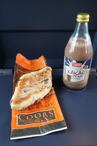 Dinkel-Rosinen-Brötchen von der Bäckerei Coors (Osnabrück Hbf) mit Kakao Drink als Frühstück auf Zugfahrt nach Den Haag