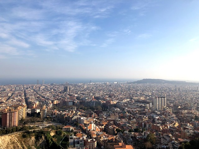 A wide-shot of Barcelona and the coastline behind it.