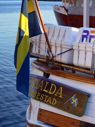 A boat from Grebbestad in Sweden, with two yellow and blue Swedish flags