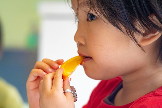 A toddler at Tysons Corner Children's Center eating an orange
