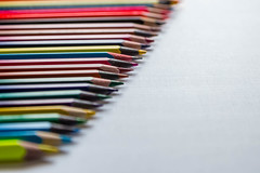 Row of colored pencils on a white background. Detail multicolored pen in line.