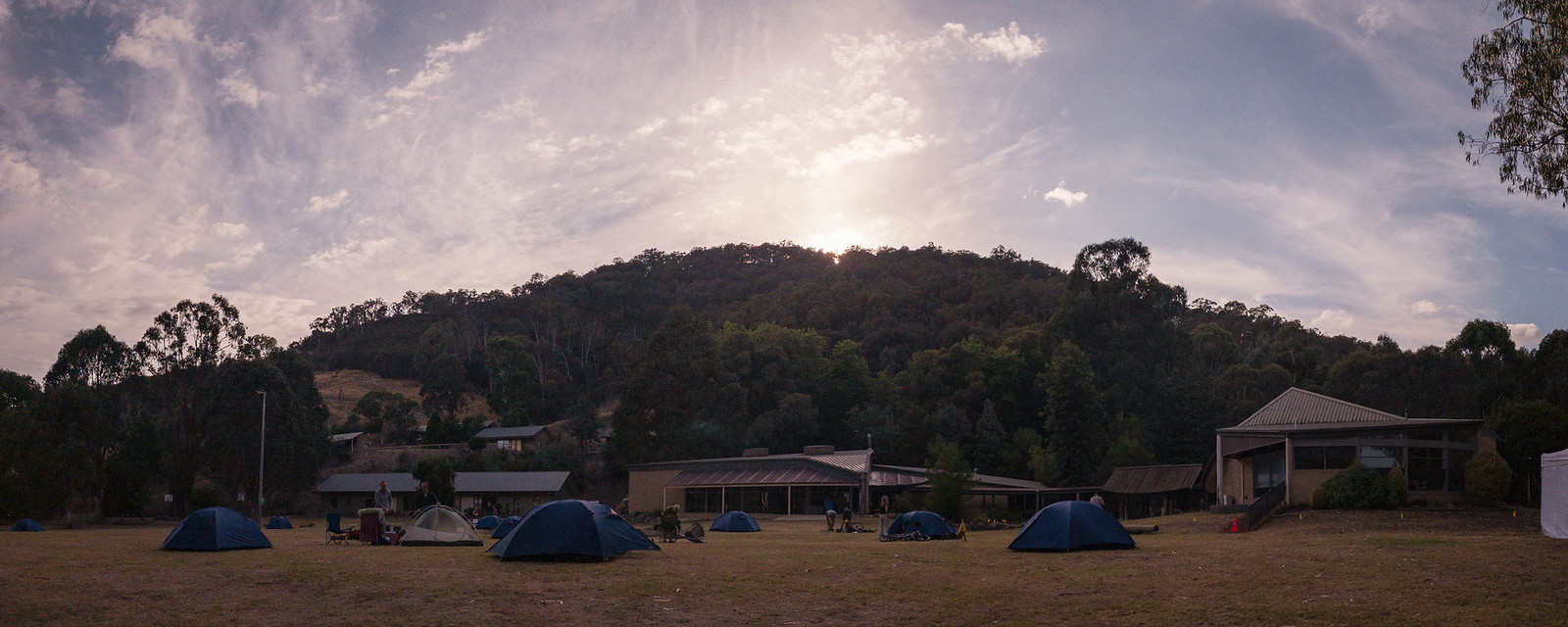 Sun rising over the mountain with blue tents in the foreground